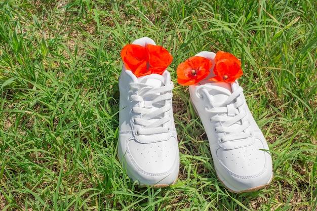 Baskets blanches sur l'herbe verte en été, coquelicots rouges à l'intérieur. le concept de neutralisation des odeurs de transpiration dans les chaussures après le port.