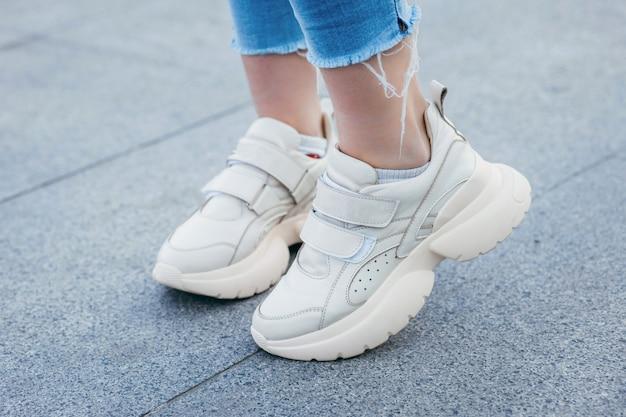 Baskets blanches sur les jambes de la fille sur le fond de la rue