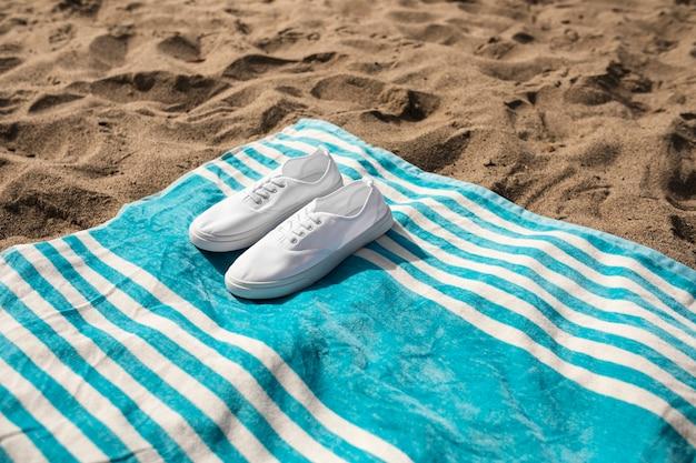 Baskets blanches sur la photographie d'ambiance d'été de serviette de plage