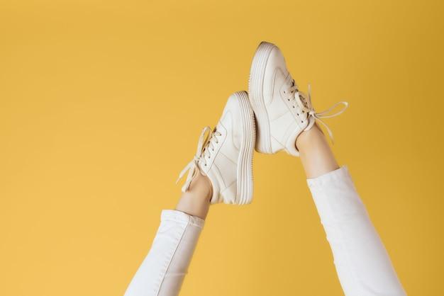 Baskets blanches de pieds féminins posant la mode de style moderne