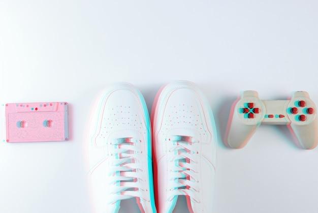 Baskets blanches de style rétro, manette de jeu, cassette audio sur blanc