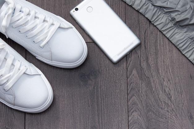 Baskets blanches avec téléphone, veste sur fond en bois marron gris. lay plat, espace de copie.
