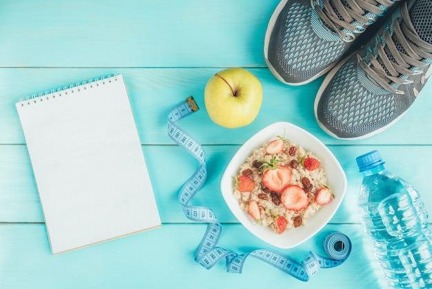 Baskets, bouteille d'eau, ruban à mesurer, flocons d'avoine avec fraise et raisins secs et pomme sur bleu, mise à plat