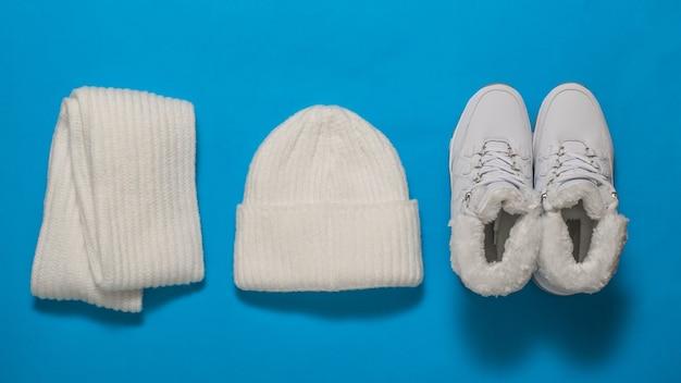Baskets chaudes blanches, une écharpe tricotée et un chapeau