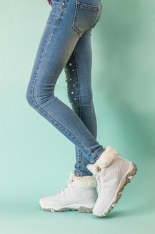 Baskets chaudes blanches sur les jambes élancées d'une fille