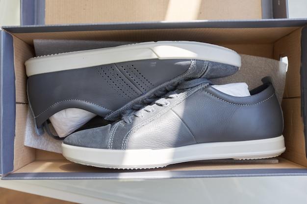 Baskets en cuir gris à la mode pour hommes, design décontracté. nouvelle paire de chaussures déballées de la boîte, achats en ligne, soldes de saison, tendances chaussures homme, boîte avec baskets à la maison