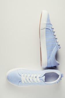 Baskets femelles à rayures bleues sur une vue de dessus de fond blanc. fond plat minimal