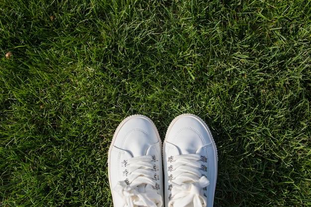 Baskets femme blanche sur l'herbe verte par une journée ensoleillée.