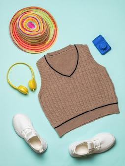 Baskets, gilet, chapeau, appareil photo et casque sur fond bleu.