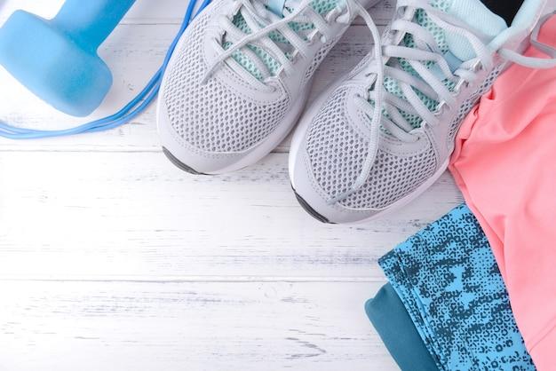 Baskets grises, haltères bleus, vêtements de sport roses, sur une surface en bois blanche