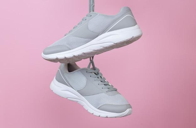 Baskets grises de sport féminin pour courir ou fitness accroché sur fond rose