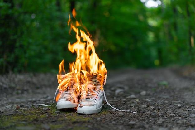 Baskets hautes blanches brûlant sur une route rurale qui court dans la forêt.