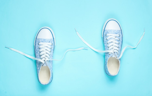 Baskets à la mode avec lacets déliés sur bleu. vue de dessus