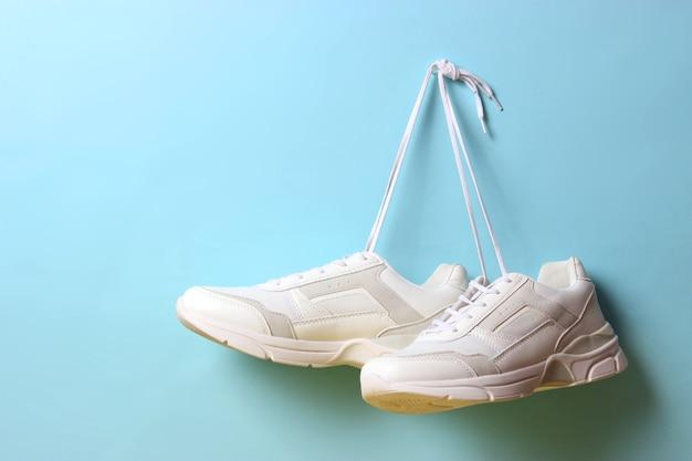 Baskets à la mode modernes accrochées aux lacets sur un fond coloré chaussures de sport chaussures de sport