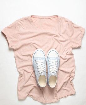 Baskets à la mode se trouvent sur le t-shirt sur blanc, vue de dessus