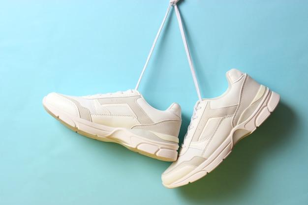 Des baskets modernes à la mode s'accrochent à des lacets sur un fond coloré. chaussures décontractées, chaussures de sport. place pour insérer text.v. photo de haute qualité
