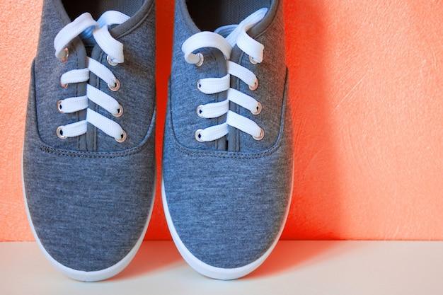 Baskets neuves grises sur fond corail. chaussures décontractées urbaines pour jeunes à la mode