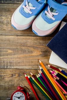 Baskets pour enfants, livres, crayons de couleur et réveil sur fond de bureau en bois