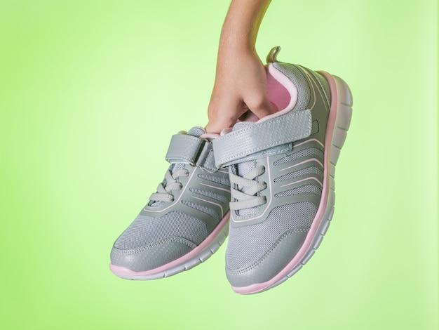 Baskets de remise en forme dans la main de l'enfant sur le vert. chaussures de sport.