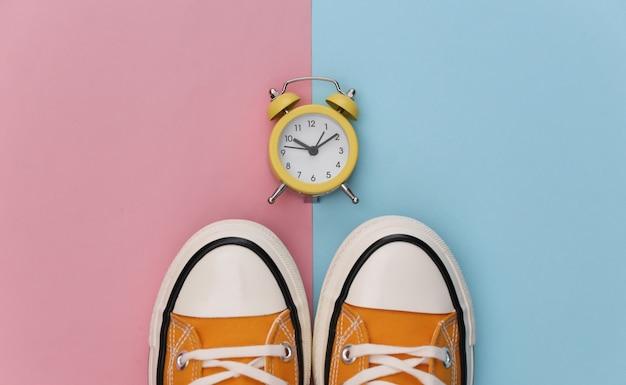 Baskets rétro jeunesse et mini réveil sur fond bleu-rose pastel.