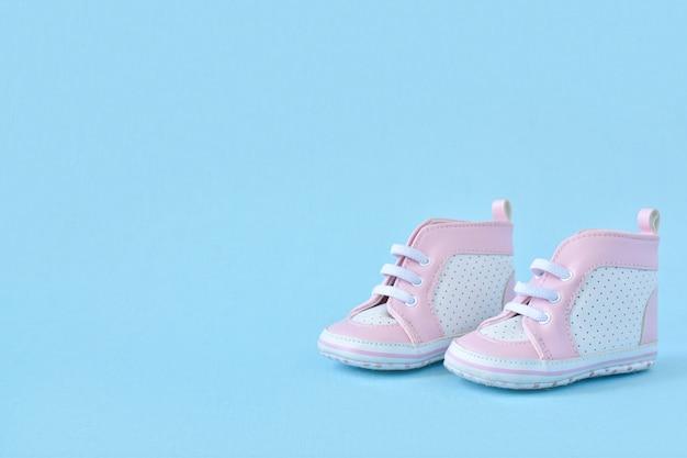 Baskets roses pour enfants sur une surface bleu clair