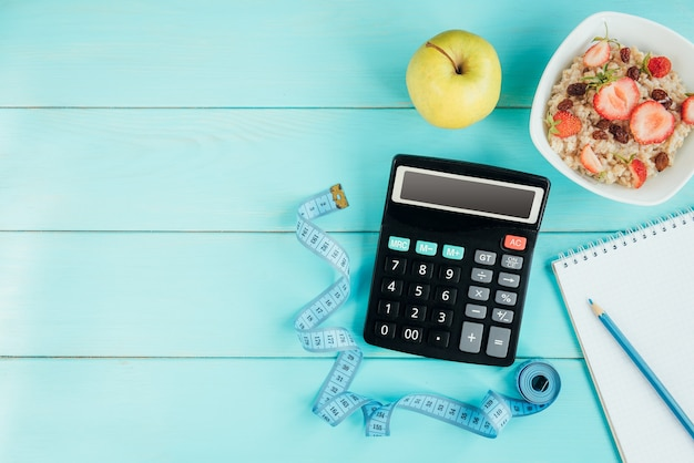 Baskets, ruban à mesurer, ordinateur portable, calculatrice, bouteille d'eau, pomme et flocons d'avoine avec fraise et raisins secs sur fond bleu, plat
