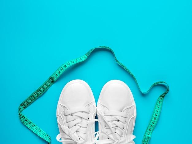 Les baskets sont noués avec des mesures sur un fond bleu. le concept d'un mode de vie actif, la disposition de l'appartement. promotion de la marche et perte de poids supplémentaire. vue de dessus.