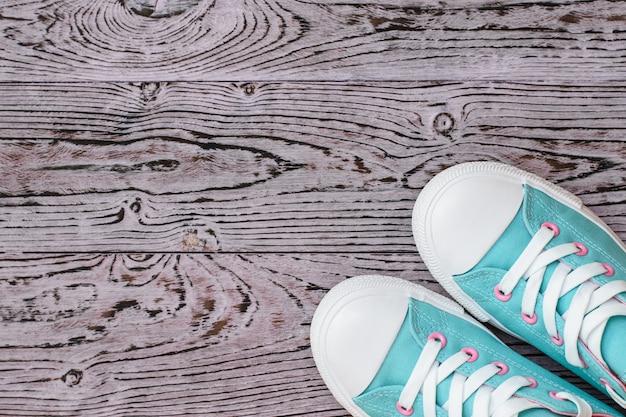 Baskets turquoises et roses sur le plancher en bois.