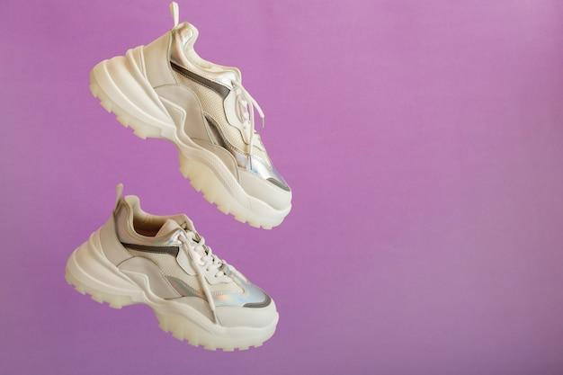 Les baskets urbaines au néon blanc volent sur fond violet de couleur avec espace de copie. baskets de sport blanches chaussures lévitation. paire de baskets sport femme.