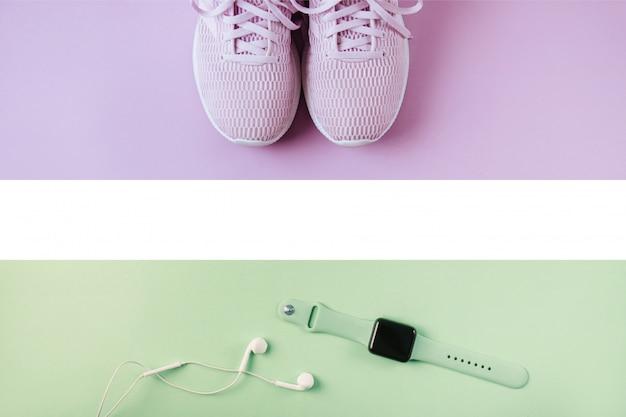 Baskets violettes, écouteurs et montres sur fond rose.
