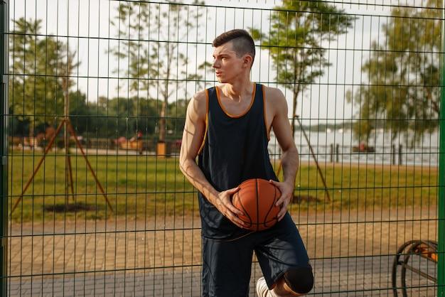 Basketteur debout à la clôture en maille