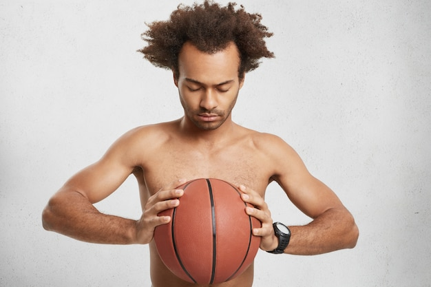 Un basketteur sérieux et concentré tient le ballon, prie pour avoir de la chance pendant le match