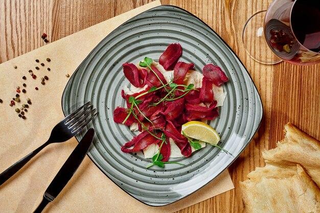 Basturma épicé tranché séché à l'air avec pain plat et vin rouge