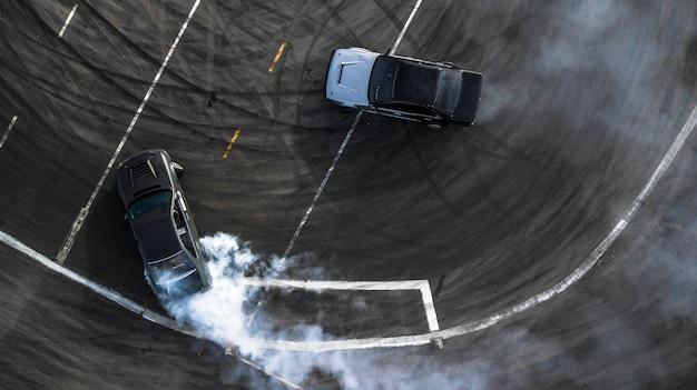 Bataille de dérive vue aérienne, deux voitures dérivent bataille sur piste de course avec de la fumée.