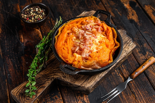 Batata de patate douce cuite au four avec du fromage et du bacon. fond en bois sombre. vue de dessus.