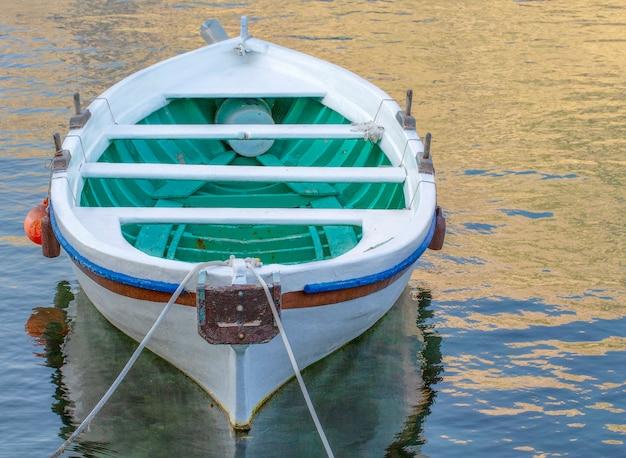 Le bateau amarré blanc sur une rivière est océan avec corde et réflexion