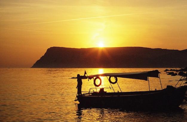 Bateau au bord de la mer au coucher du soleil