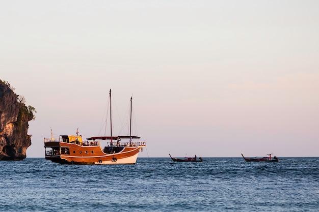 Un bateau en bois à l'ancienne navigue sur la mer. a proximité se trouvent deux petits bateaux long-courriers.