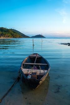 Bateau en bois au large des côtes d'une île tropicale. soirée, coucher de soleil dans l'océan. paysage tropical. les vagues de lumière secouent le bateau