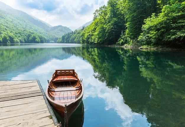 Bateau en bois au quai sur le lac de montagne