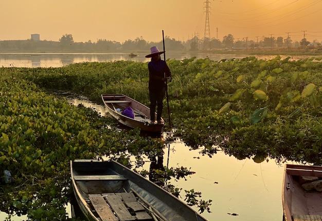 Bateau en bois aviron pêcheur au coucher du soleil