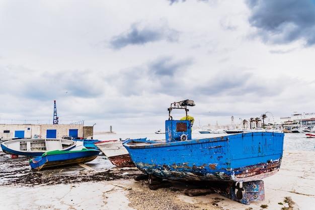 Bateau en bois bleu lavé par le temps et les vagues dans un port.