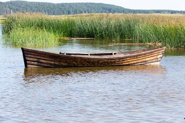Bateau En Bois Flottant Près De L'herbe Et Des Roseaux Du Lac Est Un Vieux Bateau En Bois Utilisé Pour La Pêche Par Les Villageois, Gros Plan Photo Premium