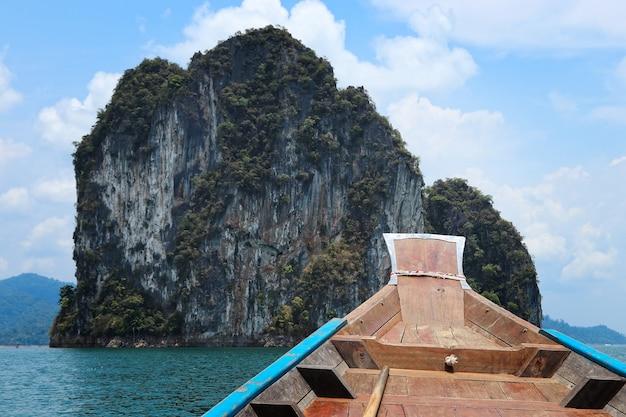 Bateau en bois sur la mer entouré de formations rocheuses sous un ciel bleu nuageux