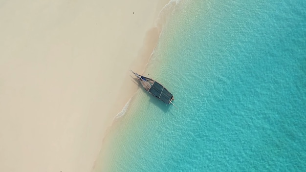 Bateau en bois sur le rivage sablonneux eau claire turquoise