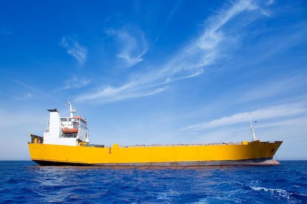 Bateau cargo ancré jaune en mer bleue