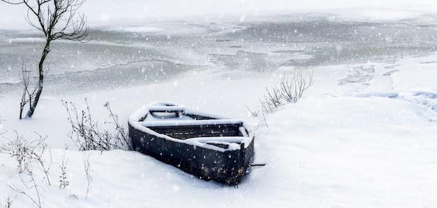 Bateau couvert de neige sur la rivière en hiver lors d'une chute de neige