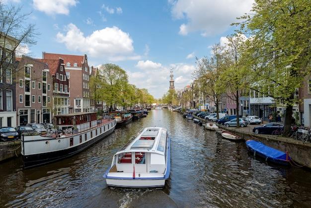 Bateau de croisière sur le canal d'amsterdam avec maison traditionnelle néerlandaise à amsterdam, pays-bas.