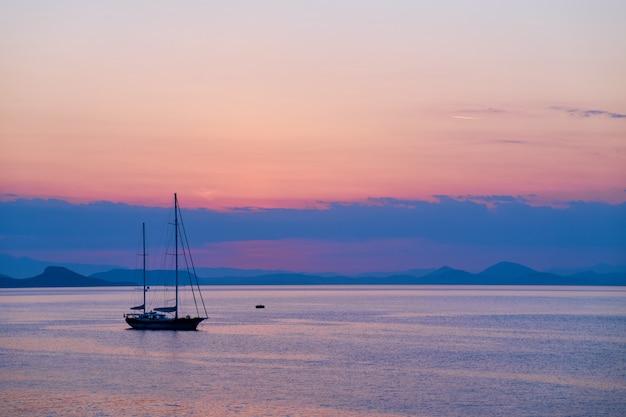 Le bateau de croisière navigue sur fond de coucher de soleil orange