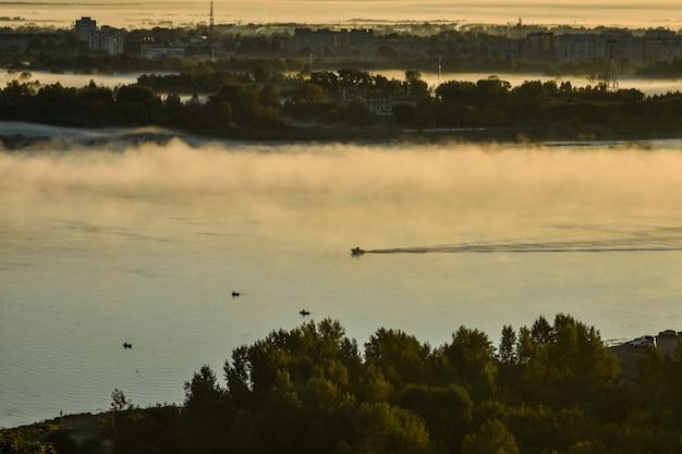Le bateau flotte sur la rivière à travers le brouillard